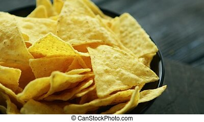 Plate full of nachos - Closeup black plate full of crunchy...