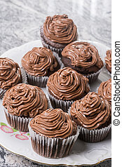 Plate full with chocolate cup cakes and with ganache chocolate cream