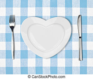 plate in shape of heart, table knife and fork on blue ...