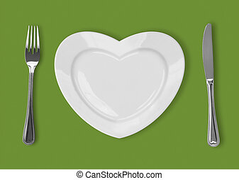 plate in shape of heart, table knife and fork on green background