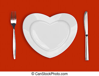 plate in shape of heart, table knife and fork on red...