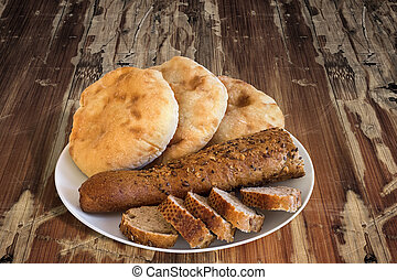 Plate of Baguette Integral Bread Sliced with Pita Bread Loafs on old Wooden Table