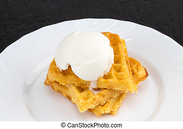 Plate of belgian waffles with ice cream on dark background