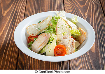 Plate of caesar salad with chicken on wooden table