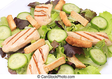 Plate of caesar salad with cucumbers.