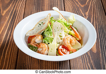 Plate of caesar salad with prawns on wooden table
