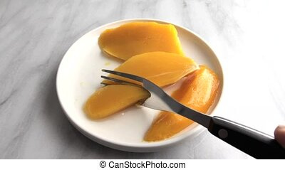 Plate of canned mangos being eaten - Video of a plate of...