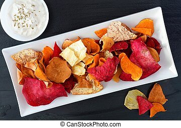 Plate of colorful healthy vegetable chips with dip, above view on a slate background