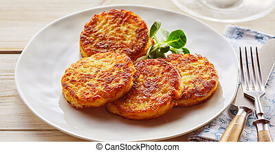 Plate of crispy golden fried potato fritters with watercress...