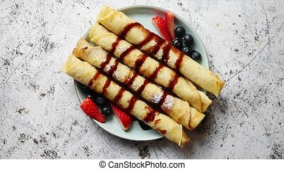 Plate of delicious crepes roll with fresh fruits and...