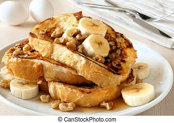 Plate of delicious French toast with bananas, walnuts and dripping maple syrup