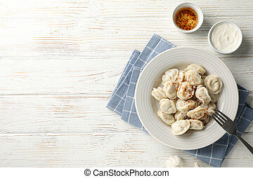 Plate of dumplings with spices on white wooden background, space for text