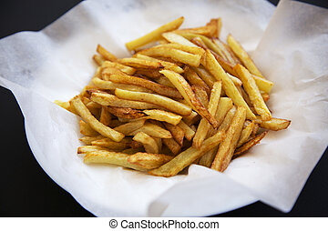 Plate of french fries on dark background, side view, close up