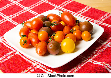 Plate of fresh mixed tomatoes on red cloth