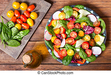 plate of fresh salad on wooden table