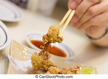 Plate of fried calamari served and chopstick with hand