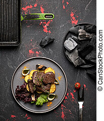 Plate of grilled meat and potatoes on black background of rustic kitchen table with grill pan and charcoal on it. Blank for restaurant advertising banner. Top view. Vertical format 4x5. Copy space
