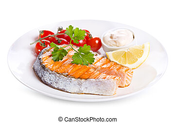 plate of grilled salmon steak with vegetables on white...