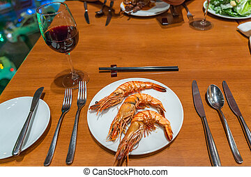 Plate of grilled shrimps and set of tableware in restaurant