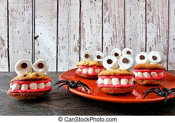 Plate of Halloween monster cookies against white wood