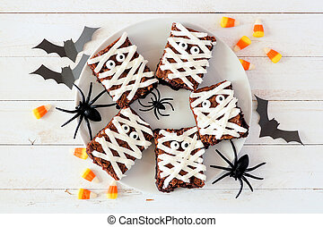 Plate of Halloween mummy brownies, top view with decor on white wood