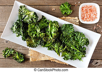 Plate of healthy organic kale chips, top view on wood