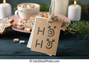 Plate of homemade Christmas cookies, coffee, marshmallows, Ho-Ho on wooden table, against blue background, space for text. Closeup
