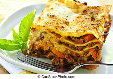 Plate of lasagna - Serving of fresh baked lasagna on a plate
