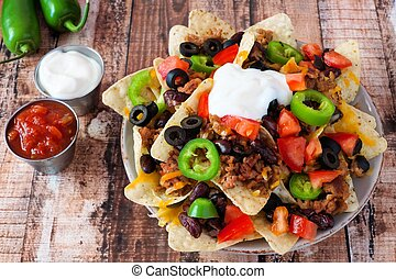 Plate of Mexican nacho chips topped with sour cream, ground meat, jalapenos, tomatoes, beans and melted cheese