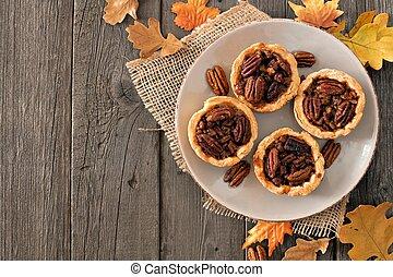 Plate of mini pecan pie tarts, rustic overhead table scene on a wood background