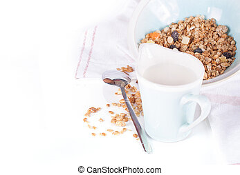 plate of muesli and milk jug on a white background