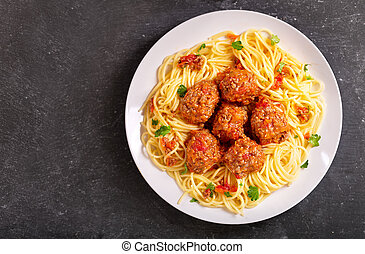 plate of pasta with meatballs on dark table