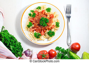 plate of pasta with tomato sauce and fork with ingredients for cooking on white background, top view with copy space.