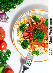 plate of pasta with tomato sauce on white background.
