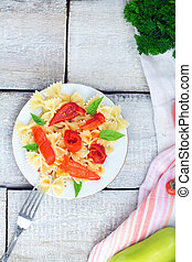 plate of pasta with tomato sauce with ingredients for cooking on white wooden background, top view with copy space
