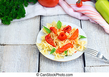 plate of pasta with tomato sauce with ingredients for cooking on white wooden background, top view with copy space.