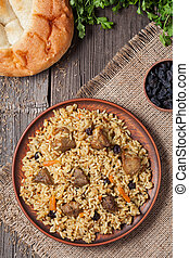 Plate of pilaf, traditional turkish spicy food with rice, fried meat, carrot onion and parsley. Served with fresh backed bread, raisins and vegetables.
