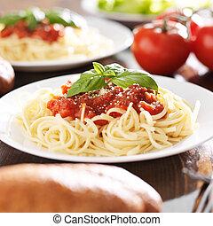 plate of spaghetti with basil garnish.