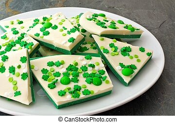 Plate of St Patricks Day chocolate candy bark with shamrock sprinkles over a slate background
