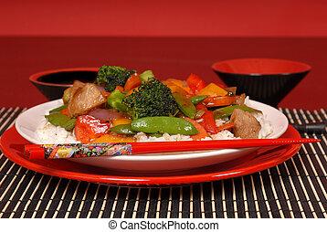 Plate of stir fry pork with chop sticks