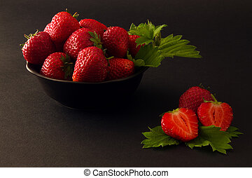 plate of strawberries with leaves on a black background.