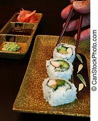 Plate of sushi, using chopsticks