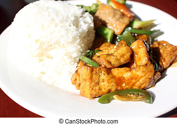 Plate of vegan Chinese food with tofu, seitan with broccoli...