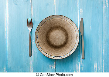 Plate on blue wooden background with utensils