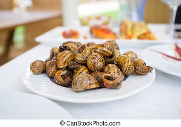 Plate on table full of fried snails