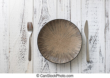 Plate on white wooden background with utensils
