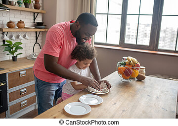 Tall dark-skinned man in a pink tshirt and his kid wiping the plate