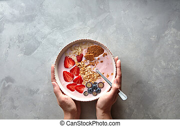 Plate with a spoon and an apetitic yoghurt with berries and almonds women's hands holding on a gray concrete background
