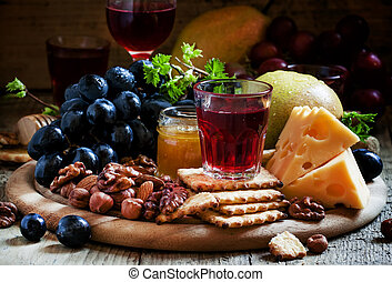 Plate with appetizers guilt: black grapes, cheese, crackers, pears, nuts, honey, almonds, on a dark wooden background, selective focus
