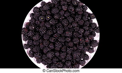 Plate with blackberry rotating on a black background...